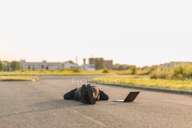 Портрет бизнесмена, лежащего на дороге с ноутбуком — стоковое фото