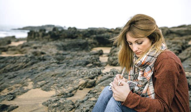 Woman with notebook sitting on rocks on the beach in winter — Stock Photo