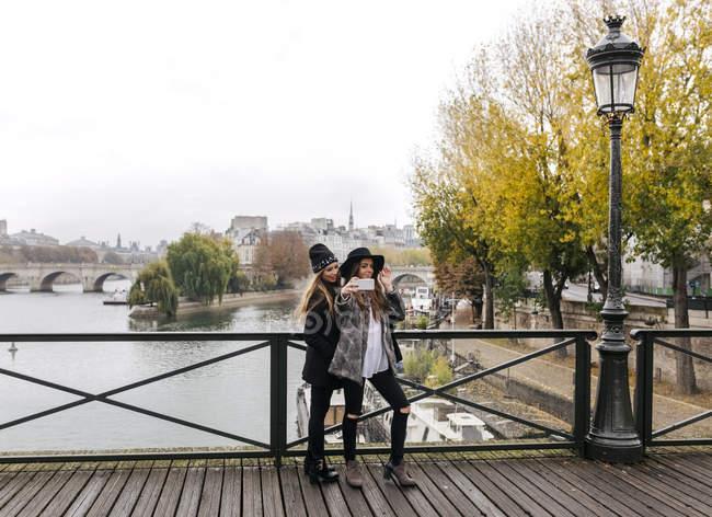Париж, Франція, дві жінки туристів бере на selfie на мосту через річку Сену — стокове фото