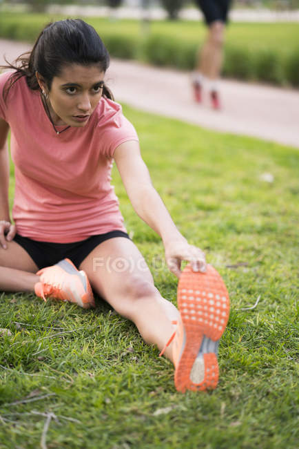 Fille d'étirement avant de courir sur la pelouse d'herbe — Photo de stock