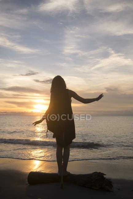 Indonesien, bali, eine Frau beobachtet den Sonnenuntergang über dem Ozean, wie sie auf einem Baumstamm balanciert — Stockfoto