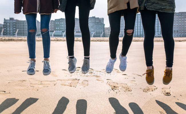 Legs of four young women jumping on sandy beach — Stock Photo
