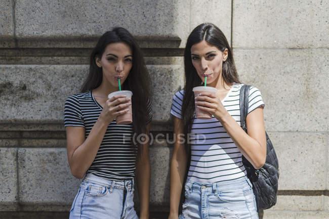 Gemelle che tengono bevande da asporto — Foto stock