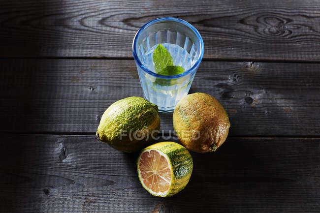 Citrons de tigre entières et tranchées et verre de l'eau infusée — Photo de stock