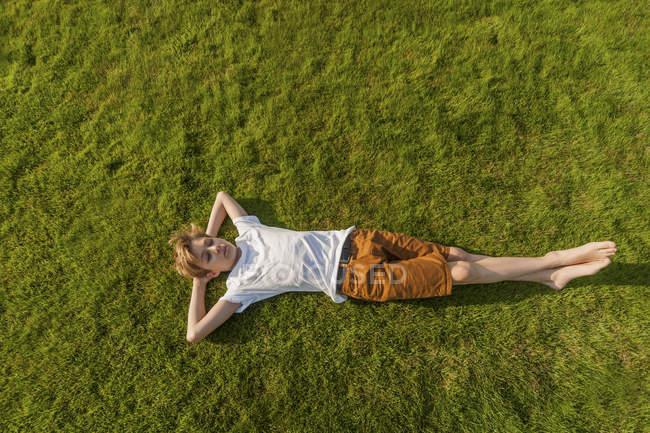 Мальчик-подросток лежит на траве с руками за головой — стоковое фото