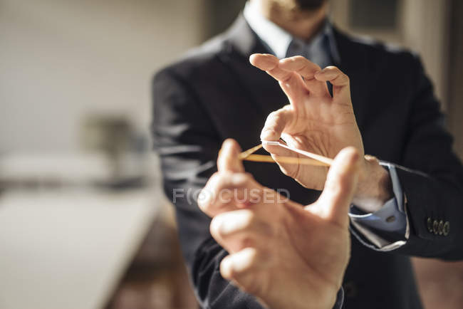 Cropped portrait of businessman using rubber band as slingshot — Stock Photo
