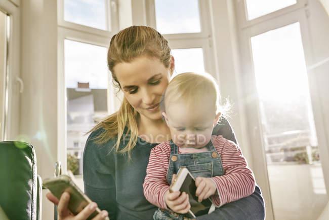 Mãe e bebê menina segurando telefones celulares — Fotografia de Stock