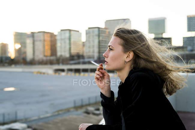 Vue de côté de fille fumer appréciant le paysage urbain — Photo de stock