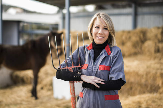 Жіночий фермер проведення сіно вилки з конем на тлі — стокове фото