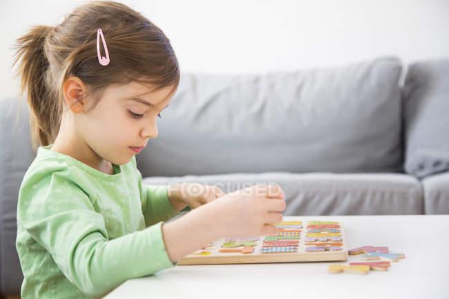 Маленькая девочка изучает алфавит с деревянными буквами дома — стоковое фото