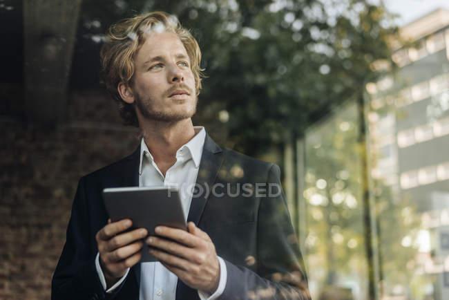 Geschäftsmann mit Tablet wegsehen hinter Fensterscheibe — Stockfoto