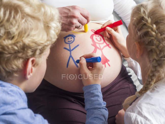 Дети рисуют на животе беременной матери — стоковое фото