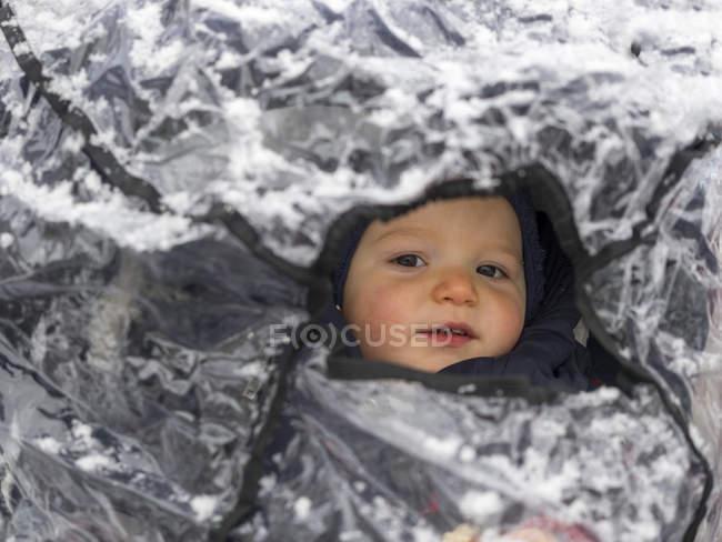 Ragazzino che guarda fuori dal rifugio antipioggia innevato della sua carrozzina — Foto stock