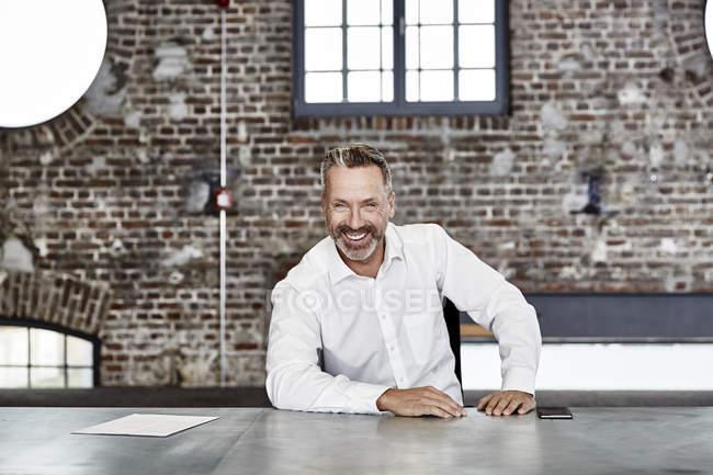 Uomo d'affari che si siede al tavolo nel loft — Foto stock