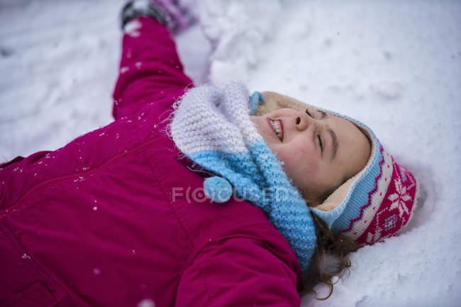 Ragazza sorridente che fa un angelo di neve in inverno — Foto stock