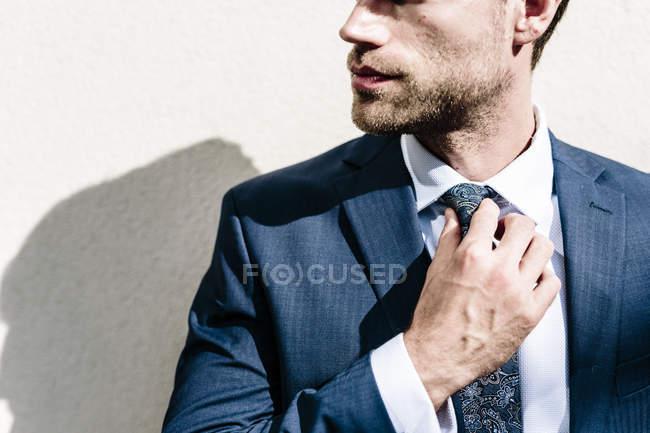 Businessman fixing tie — Stock Photo