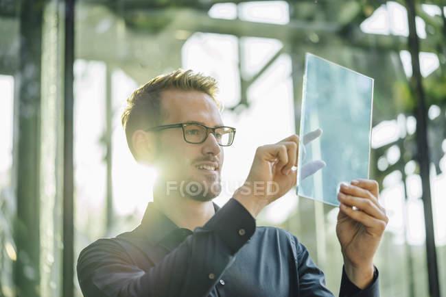 Retrato de empresário segurando tela de vidro dentro de casa — Fotografia de Stock
