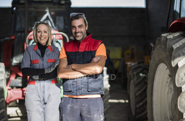 Couple of farmers standing in front of tractor with arms crossed — Stock Photo