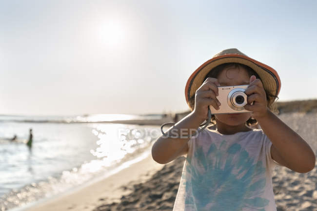 Little girl taking picture on camera, Son Bou beach, Balearic Islands, Spain — Stock Photo