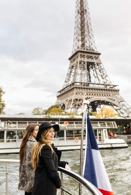 Paris, France, two female tourists taking a cruise on the Seine River with the Eiffel Tower in the background. — Stock Photo