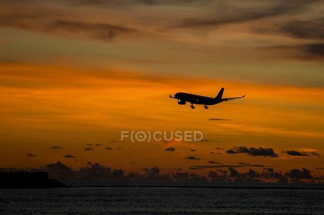 Indonesia, Bali, airplane in the sky and sunset over the ocean — Stock Photo