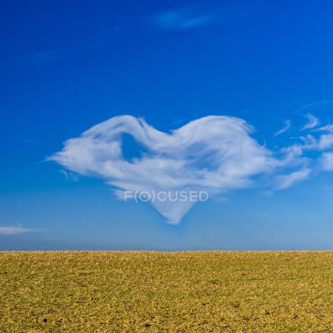 Heart-shaped cloud on blue sky — Stock Photo