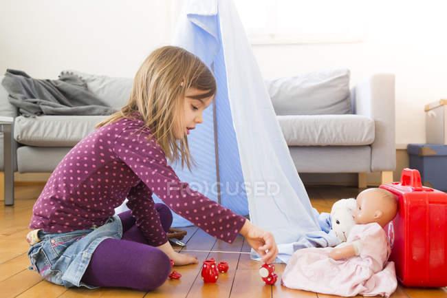 Маленька дівчинка, граючи кава-учасниця в іграшки на підлозі будинку — стокове фото