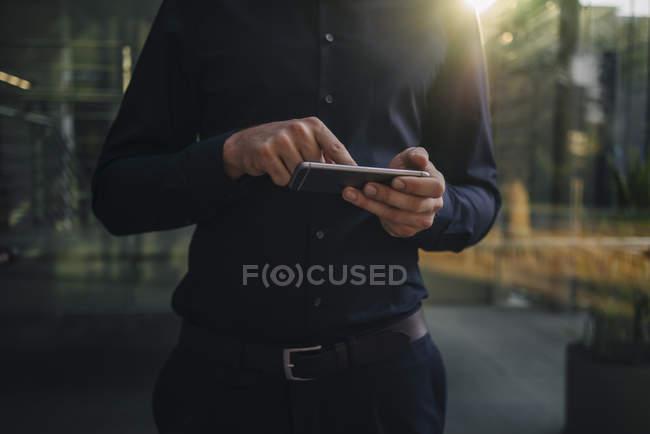 Ritratto ritagliato di uomo d'affari utilizzando smartphone — Foto stock