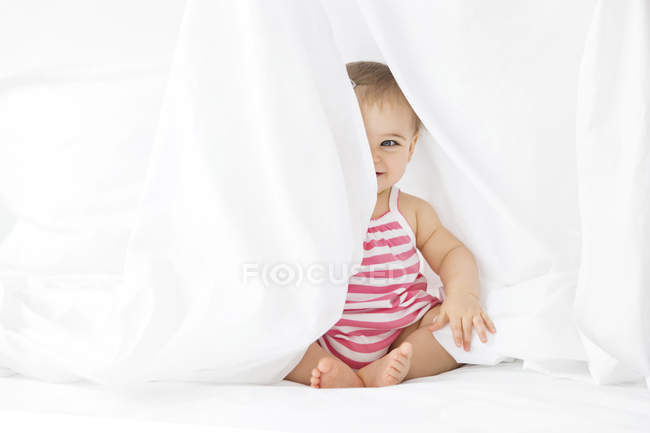 Bebê sentado numa cama branca, brincando de esconde-esconde debaixo do lençol — Fotografia de Stock