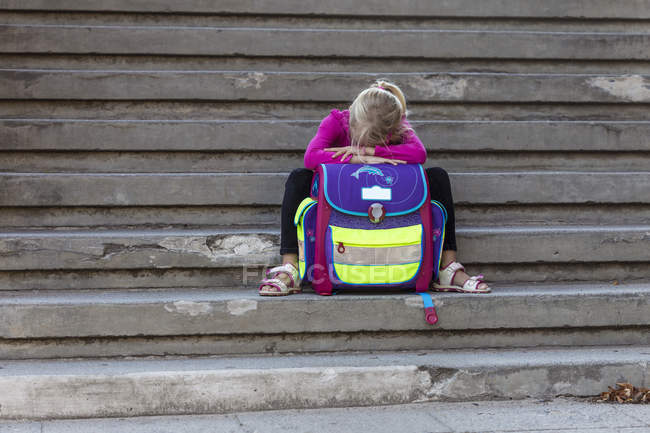 Triste uma menina sentada na escada com a mochila da escola — Fotografia de Stock