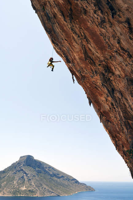 Portrait of male climber hanging on rope near rock wall — Stock Photo