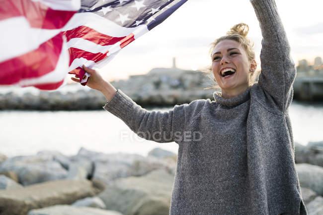 Молода жінка з розмахуючи американський прапор — стокове фото