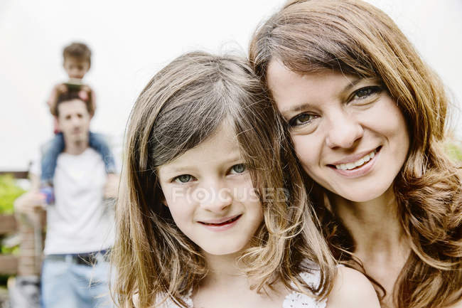 Happy family hugging in the garden, portrait — Stock Photo