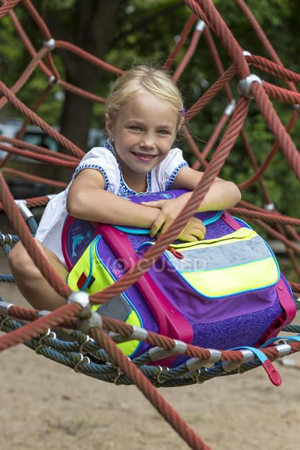 Retrato de menina sorridente com saco de escola sentado no ninho balanço playground — Fotografia de Stock
