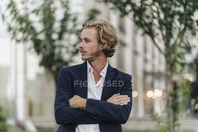 Businessman standing outdoors with arms crossed and looking away — Stock Photo