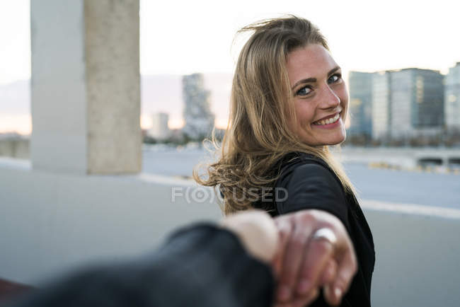 Молода жінка тримає в руці, дивлячись на камеру — стокове фото