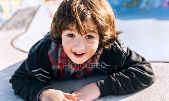 Милый мальчик улыбается и смотрит в камеру — стоковое фото