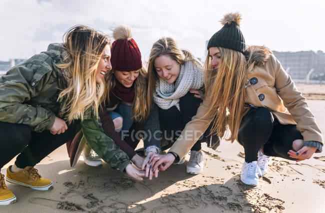 Vier Freunde, die sich die Hand am Sandstrand — Stockfoto