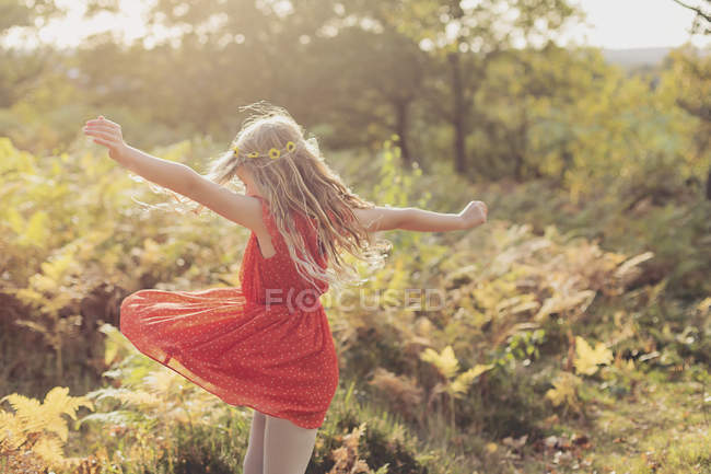 Little girl wearing red summer dress dancing in nature — Stock Photo