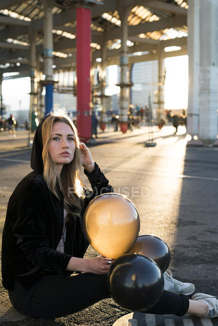 Urban scene with girl sitting down with air baloons — Stock Photo