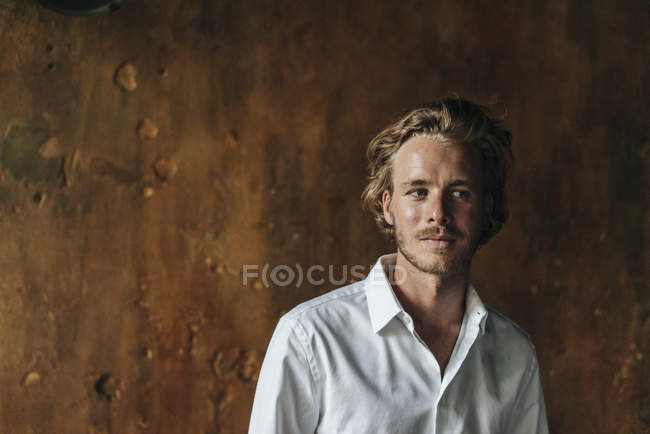 Portrait of blond man wearing white shirt standing in front of brown plaster — Stock Photo