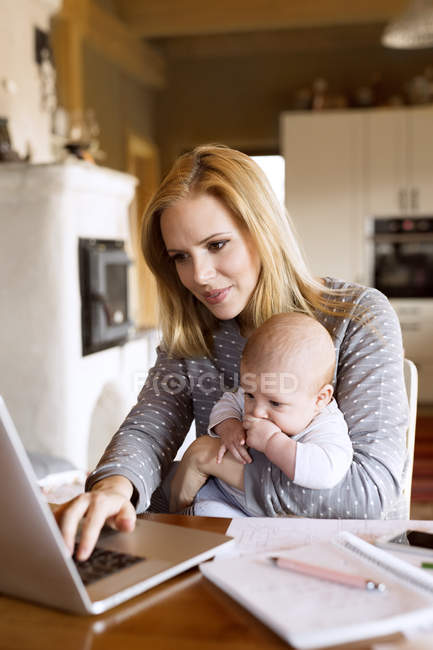 Mother with baby at home using laptop — Stock Photo
