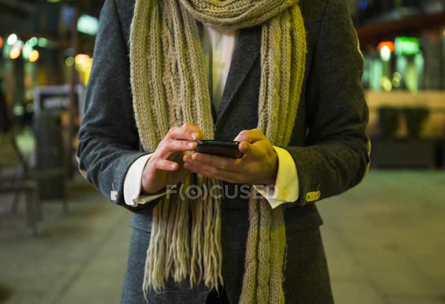 Gros plan d'un homme qui utilise un téléphone cellulaire en ville la nuit — Photo de stock