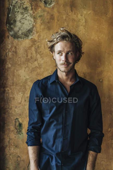 Усміхаючись бізнесмен, що стоїть перед зруйнованому стіни — стокове фото