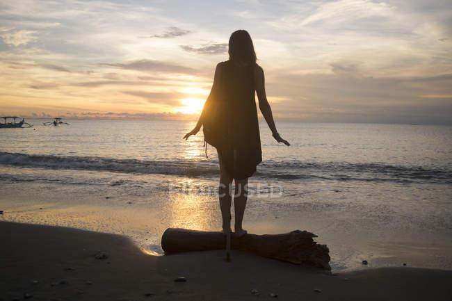 Indonésie, Bali, femme regardant le coucher du soleil sur l'océan — Photo de stock