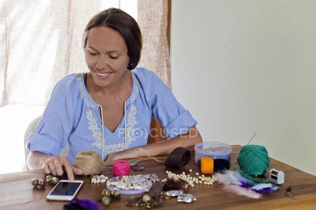 Mulher usando telefone celular e fazendo artesanato na mesa de madeira — Fotografia de Stock