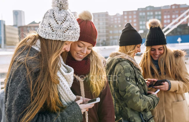 Four young women texting with smartphones in city — Stock Photo