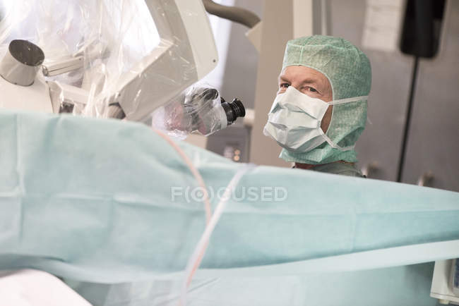 Cropped portrait of neurosurgeon with microscope in operation room — Stock Photo