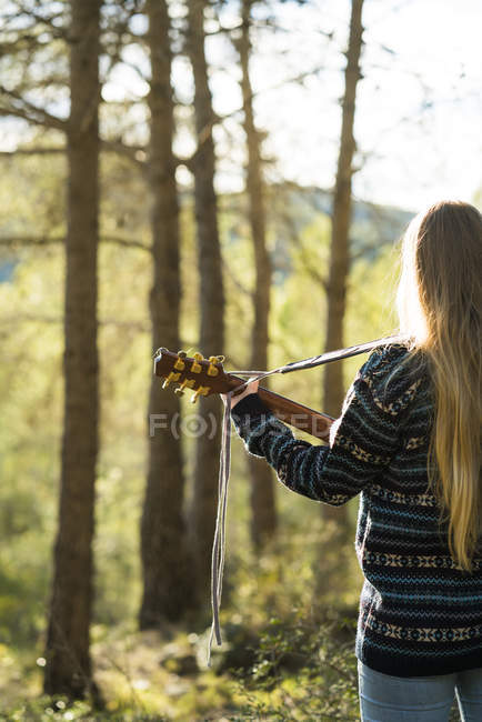 Woman playing guitar in nature — Stock Photo