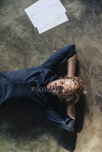 Замислений чоловік лежить на підлозі поруч із документів — стокове фото